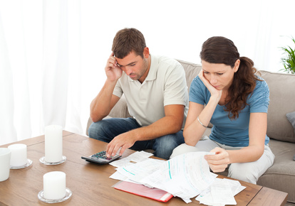 Desperate couple doing their accounts sitting on the sofa at home